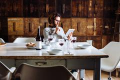 Young man reading digital tablet at dining table Stock Photos