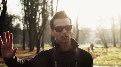 Stock Video Footage of Portrait of young man in sunglasses, jacket reads a rap in autumn park. Gesture