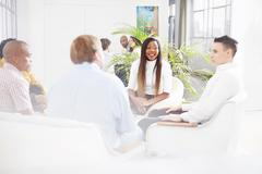 Colleagues in office sitting chatting, smiling - stock photo