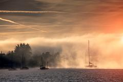 Boats in mist, Lake Maggiore, Piedmont, Lombardy, Italy Stock Photos