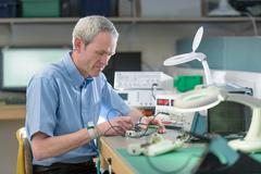 Electronics engineer assembling components in electronics factory Stock Photos
