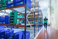 Worker in storage area of electronics factory Stock Photos