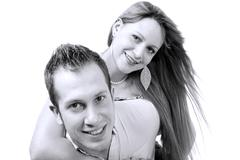 cheerful young couple in love in black and white background - stock photo