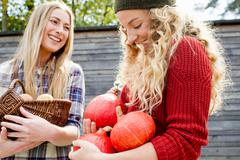 Two women holding homegrown produce Stock Photos