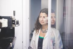 Female scientist monitoring motor alignment on x-ray diffractometer machine Stock Photos