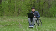 Disabled man thinks problems wheelchair with a laptop in a wheelchair working on Stock Footage