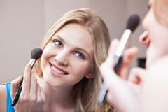 Young woman applying blusher in the mirror - stock photo