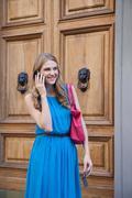 Young woman using cellphone near doors Stock Photos