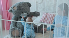 Baby playing with big teddy bear Stock Footage