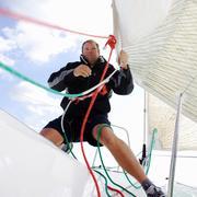 Man on yacht, pulling ropes Stock Photos