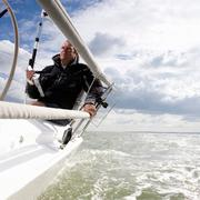 Man on yacht, with navigation aid Stock Photos