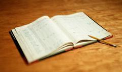 Open account book on wooden desktop - stock photo