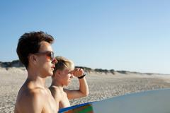 Two young surfers heading to the sea - stock photo