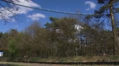 Squirrel bridge spanning road + traffic passing below - low angle Stock Footage