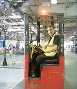 Portrait of apprentice fork lift truck driver in car factory Kuvituskuvat