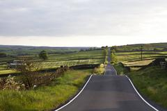 Paved road in rural landscape Stock Photos