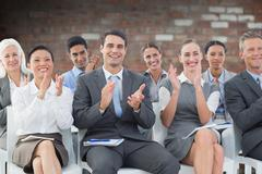 Composite image of business people applauding during meeting Stock Photos