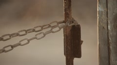 Man attaches the chain to a rusty metal pole Stock Footage