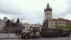 A touristic train and an old-fashioned red car in the Old Town Square in Prague Stock Footage
