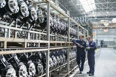 Workers inspecting large number of axles on shelving unit in car plant - stock photo