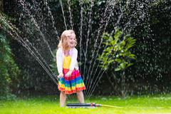 Kids playing with garden sprinkler - stock photo