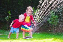 Kids playing with garden sprinkler Stock Photos