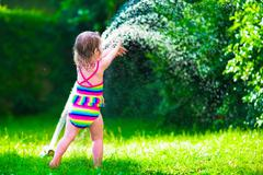 Little girl playing with garden water sprinkler - stock photo