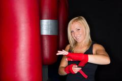Boxer wrapping her hands in gym Stock Photos