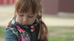 Little girl looks at the petal. - stock footage