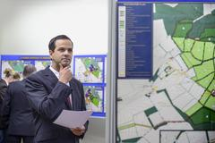 Member of public inspecting proposed planning inquiry in town hall Stock Photos