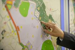 Member of public pointing at map of proposed planning inquiry in town hall Stock Photos