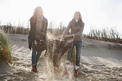 Women shaking out beach blanket Stock Photos