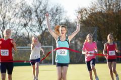 Runner crossing finish line in field Stock Photos