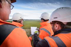 Workers holding plans inspecting land around surface coal mine restoration - stock photo
