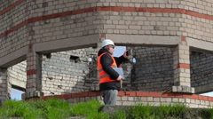 Civil engineer walking and filming on tablet PC near building Stock Footage