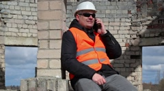 Civil engineer sitting and talking on smart phone Stock Footage