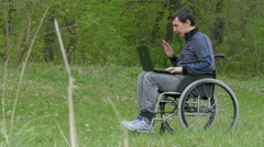 Disabled man video chat conversation wheelchair with a laptop in a wheelchair Stock Footage