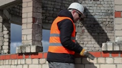 Worker with sledgehammer near brick wall Stock Footage