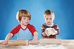 Boys rolling out dough - stock photo