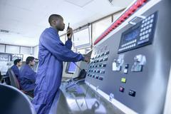 Workers in control room of car factory, one worker using walkie talkie at Kuvituskuvat
