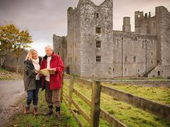 Couple with map visiting Bolton Castle, a 14th century Grade I listed building - stock photo