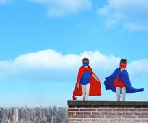 Composite image of masked kids running pretending to be superheroes - stock photo