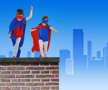 Composite image of masked kids walking pretending to be superheroes - stock photo