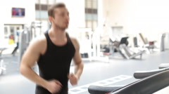 Fit athletic man is starting to run on the treadmill in the sport gym - stock footage