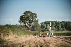 Workers in field looking for coal seams with drilling rig at surface coal mine Stock Photos