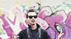 Man in sunglasses, sway gesture, sing in camera. Artist. Graffiti wall on Stock Footage