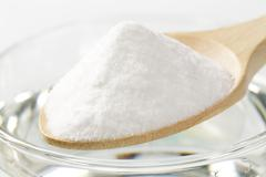 spoon of baking soda and glass of water - stock photo