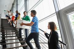 People passing boxes up stairs Stock Photos
