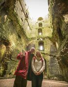 Couple in ruined walls of Bolton Castle, a 14th century Grade I listed building - stock photo