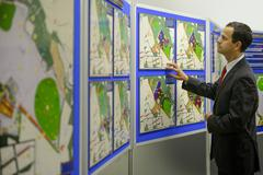 Member of public looking at maps of proposed planning inquiry in town hall Stock Photos